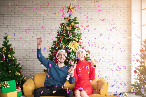 man-and-woman-wearing-santa-hats-sitting-on-sofa-popping-a-3183392